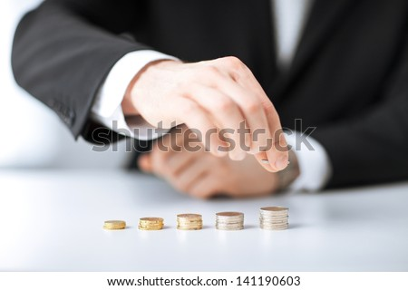 picture of man putting stack of coins into one row - stock photo