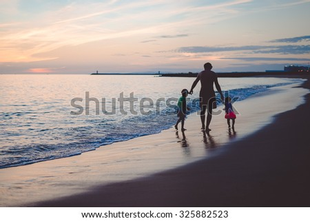 Picture of man walking with boy and girl on sunset beach. Silhouette of happy family beside seawaves on dark blue seaside outdoor background. - stock photo