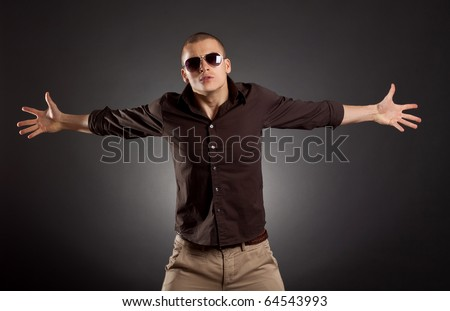 picture of man with hands spread to sides on a dark background - stock photo