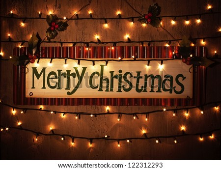 Picture of Merry Christmas banner on brown grunge door at home, happy New Year, glowing electrical garland, Christmastime house interior, congratulations postcard, holiday illumination - stock photo