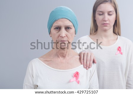 Picture of mother and daughter wearing pink ribbons, an international symbol of breast cancer awareness - stock photo