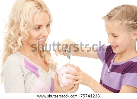 picture of mother and little girl with piggy bank - stock photo