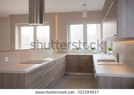 Picture of new style commodious kitchen in light colors - stock photo