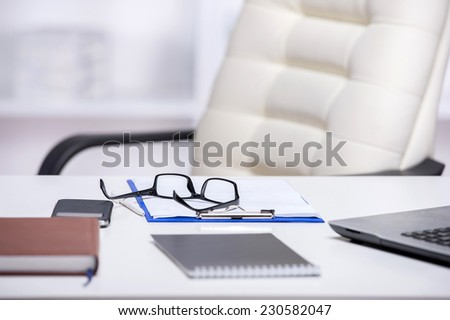 Picture of office desks and chair. Notebook, glasses, and laptop are on the table. - stock photo