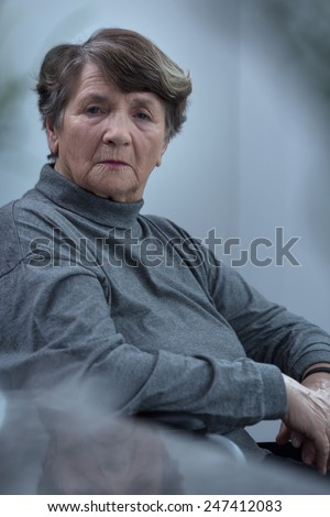 Picture of old sad woman sitting alone - stock photo