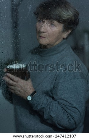 Picture of older grieved woman looking outside - stock photo