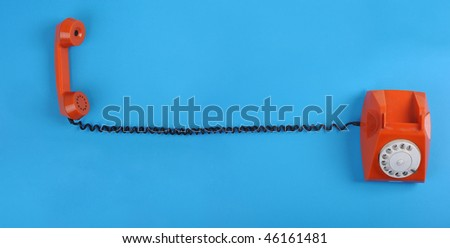 Picture of orange telephone over blue background. Many lot of copyspace - stock photo