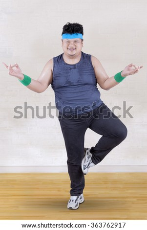 Picture of overweight person doing workout at home while standing with one feet - stock photo