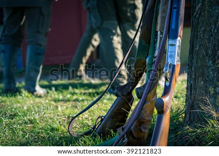 Picture of rifle in front hunters. Selective focus. - stock photo