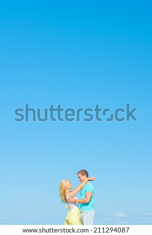 Picture of romantic young couple against blue sky. Space for text. - stock photo