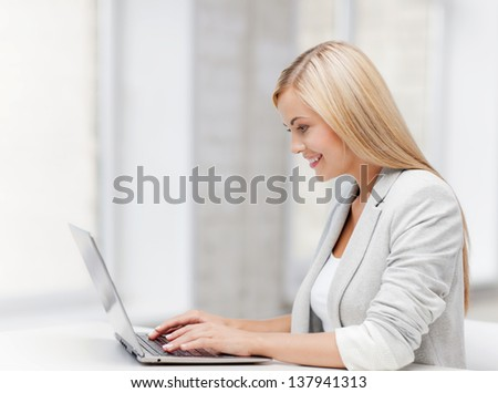 picture of smiling businesswoman using her laptop computer - stock photo