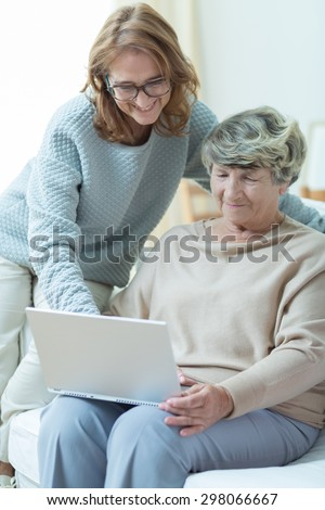 Picture of smiling carer teaching old woman computer skills - stock photo