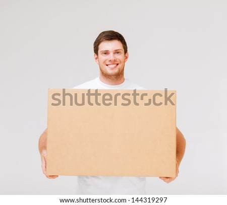 picture of smiling man carrying carton box - stock photo