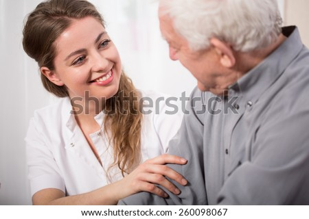 Picture of smiling nurse assisting senior man - stock photo
