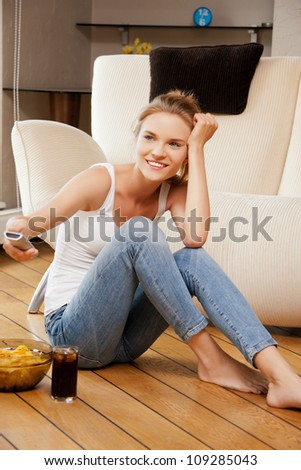 picture of smiling teenage girl with remote control - stock photo