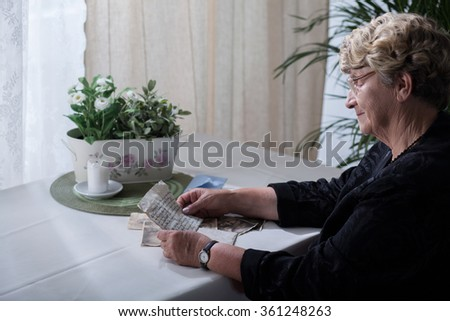 Picture of smiling widow looking over memorabilia of her husband - stock photo