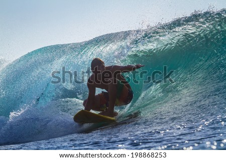 Picture of Surfing a Wave at Sunrise Time - stock photo