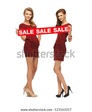 picture of teenage girsl in red dresses with sale sign - stock photo