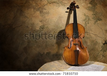 Picture of the old italian violin on a wall background - stock photo