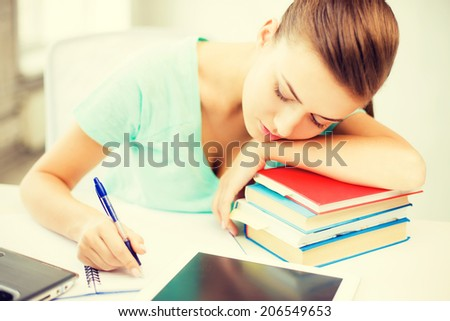 picture of tired student sleeping on stock of books - stock photo