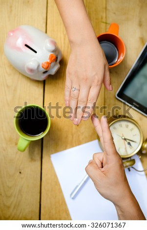 Picture of two hands gesturing above tabletop with piggy-bank and coffee mugs. Playing in rock-paper-scissors game on indoor background. - stock photo