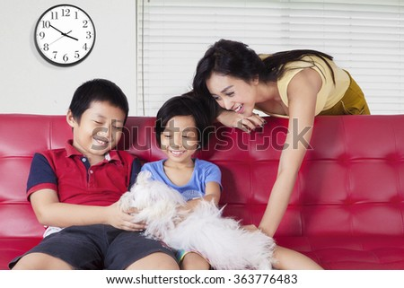 Picture of two happy children and their mother playing a maltese dog on the sofa at home - stock photo