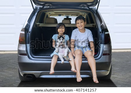 Picture of two happy children sitting in the car while holding husky dog and smiling at the camera - stock photo