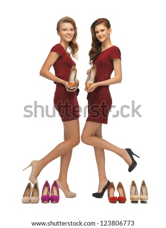 picture of two lovely teenage girls in red dresses with shoes - stock photo