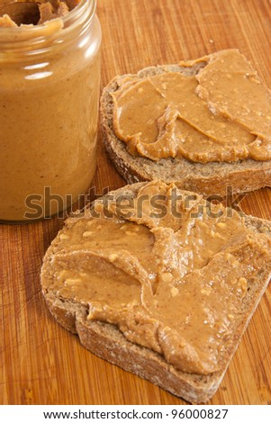 Picture of two slices of bread with peanut butter and a jar of peanut butter - stock photo