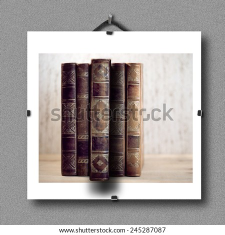 Picture of vintage books hanging on wall, with 3d illusion that one book is pulled out of the picture - stock photo