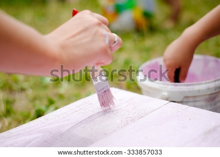Picture of woman and child's hands painting on wooden plank. Closeup of brush with pink color and paint can on blurred summer outdoor background. - stock photo