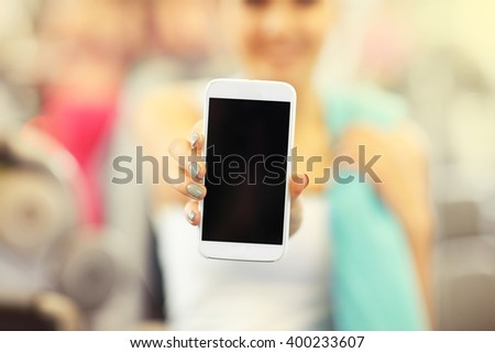 Picture of woman holding smartphone in gym - stock photo