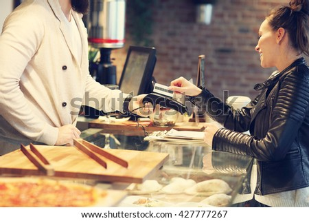 Picture of woman paying by credit card in restaurant - stock photo