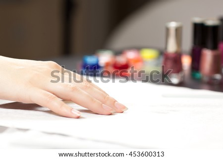 Picture of woman's hand and nail polishes at spa studio - stock photo