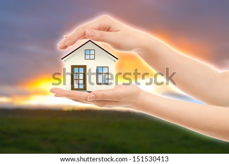 Picture of woman's hands holding a beautiful house against nature - stock photo