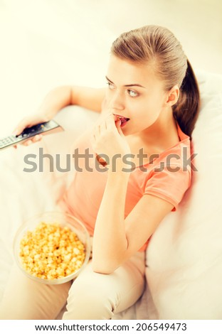 picture of woman watching tv and eating popcorn - stock photo