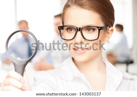 picture of woman with magnifying glass in the office - stock photo