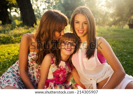 Picture of young mother kissing her children, closeup portrait of happy family, cute brunette female with two daughters outdoor in spring time, smiling faces, happiness and love concept - stock photo