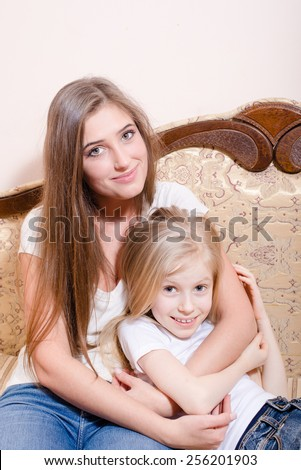 Picture of young pretty woman and little girl hugging together - stock photo