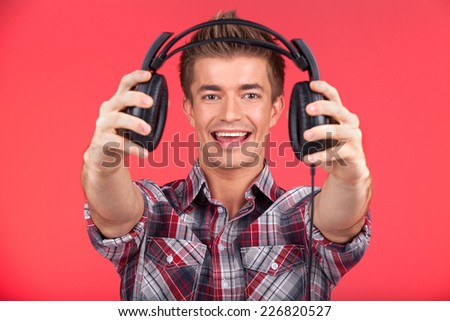 picture of young smiling man offering headphones. guy holding and giving headphones on red background - stock photo