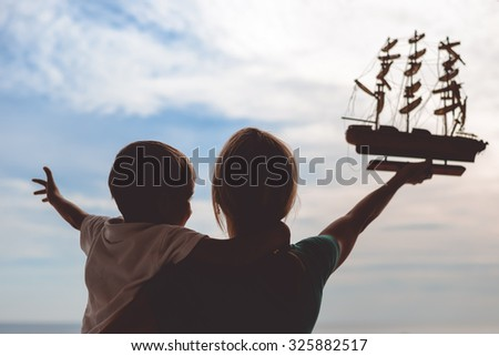 Picture of young woman and boy holding ship model. Silhouette of excited happy family on sunset sky outdoor background. - stock photo