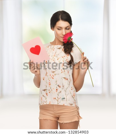 picture of young woman holding flower and  postcard. - stock photo