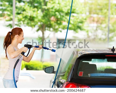 Picture, portrait young, smiling, happy, attractive woman washing automobile at manual car washing self service station, cleaning with foam, pressured water. Transportation, auto, vehicle care concept - stock photo