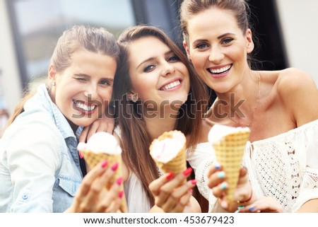 Picture presenting happy group of friends eating ice-cream outdoors - stock photo