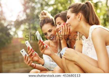 Picture presenting happy group of friends with smartphones sitting outdoors - stock photo