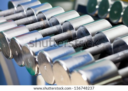 Picture shows a row of dumbbells neatly stacked on their stands. - stock photo