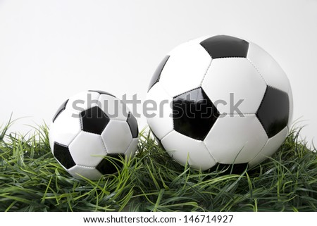 Picture shows two footballs on a green field. Tabletop with white background - stock photo