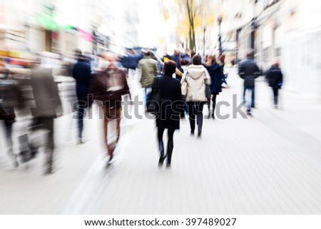 picture with creative camera made zoom effect of people walking in a pedestrian zone - stock photo