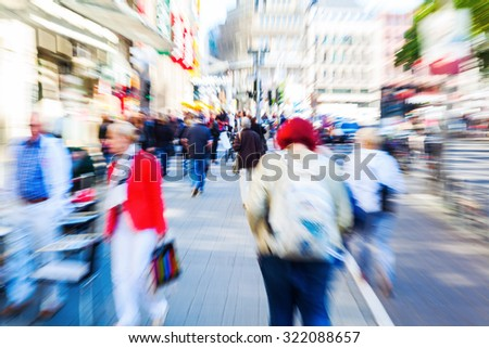 picture with creative zoom effect of people in a shopping street of a big city - stock photo