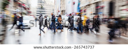 picture with zoom effect of a crowd of pedestrians crossing a street in the rainy city - stock photo